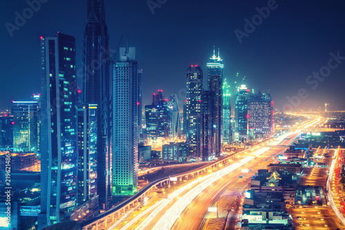 plakat Scenic nighttime skyline of downtown Dubai, United Arab Emirates. Aerial view on highways and skyscrapers in the distance.