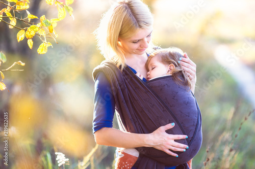 Photo  Young mother carrying her baby in a shawl sling