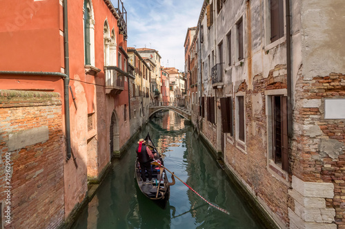 Staande foto Gondolas Venetian gondolier punting gondola through green canal waters of Venice Italy