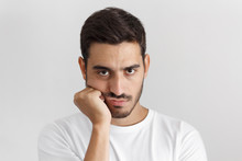 Close Up Portrait Of Bored Young Man In White Tshirt With Head On Chin Isolated On Gray Background
