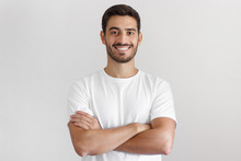 Portrait Of Smiling Handsome Man In White T-shirt, Standing With Crossed Arms Isolated On Gray Background