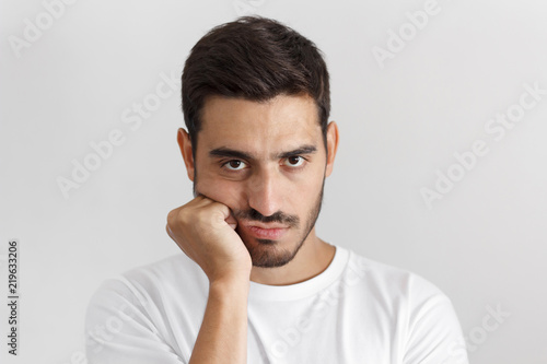 Fotografie, Obraz  Close up portrait of bored young man in white tshirt with head on chin isolated