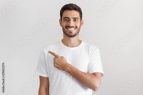 Photo Handsome man in white t-shirt pointing left with finger isolated on gray backgro