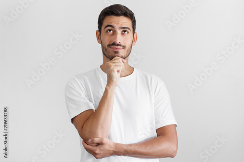 Fotografía Daylight portrait of young man with dreamy cheerful expression, thinking, isolat