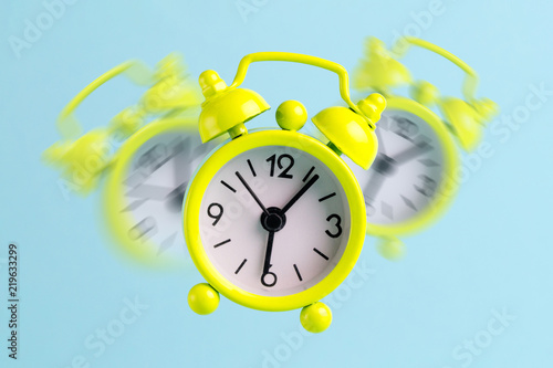 Alarm clock on a blue background. Early awakening, good morning Wallpaper Mural