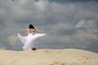 Piękna dziewczyna w białej sukni tańczy na szczycie piaszczystej wydmy, pustynia.