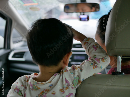 Valokuva  Asian baby standing on a driving car and refused to sitting and fastening the sa