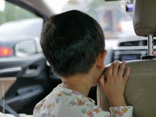 Fotografija  Asian baby standing on a driving car and refused to sitting and fastening the sa