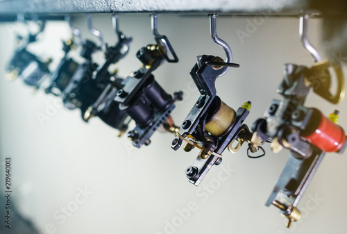 parts of coil ink tattoo machine, hanging on wooden shelf, close up ...