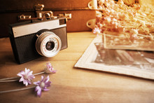 Close Up Of Old Camera Lens Over Blurredbackground Of Old Leather Suitcase,  Retro Shoots And  Flowers. Vintage Camera On Wooden Table. Retro Background, Selective Focus