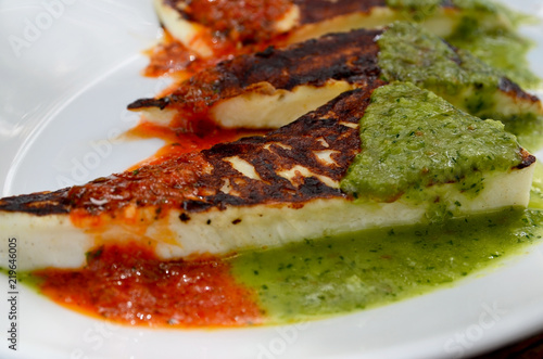 Grilled cheese with canarian sauces mojo rojo and mojo verde on a white plateclose up.Traditional tapas on Tenerife,Canary Islands,Spain.Selective focus.