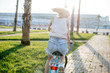 Back view of active unrecognizable woman riding fast on vintage bike in tropical park, recreation trail to hotel. Active vacation lifestyle concept.