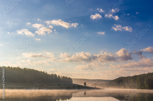 Fotografía foggy lakeside at sunrise with clouds on blue sky