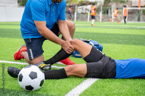 obraz dibond Footballer wearing a blue shirt, black pants injured in the lawn during the race.