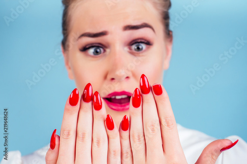 Fotografia close-up portrait of nervous unhappy young blonde woman looking at a broken fingernail and crying