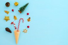 Christmas Composition.  Ice Cream Cone With Christmas Decoration On Blue Background. Creative Flat Lay, Border And Copy Space
