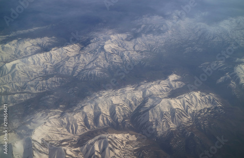 Stunning aerial view of snow capped mountain ranges view from airplane window during the flight
