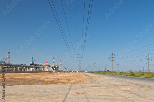 Foto op Plexiglas Industrial geb. Power line passing between broken, old asphalt road and refinery