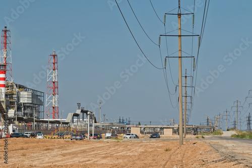Deurstickers Industrial geb. Power line passing between broken, old asphalt road and refinery