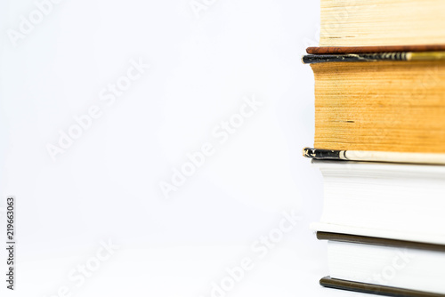 Fotografía  Column of books close up macro shot on white background, space for text
