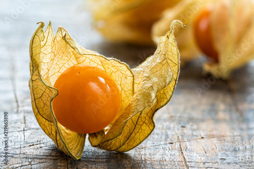 Fotografía  Physalis fruit (Physalis Peruviana) with husk on wooden background - closeup