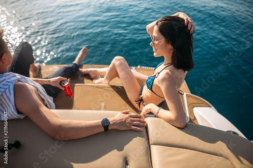 Fényképezés Travelling european wealthy married people in swimwear talking and sipping beverages while lying on a boat deck with open sea background