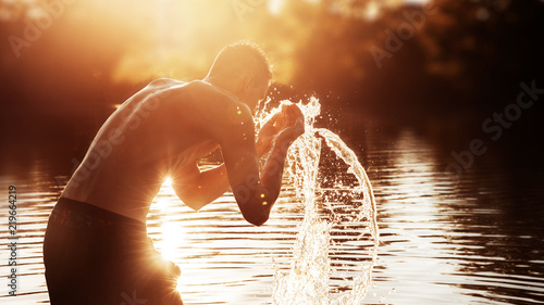 Photographie a young man is standing in a river and washing his face against the sunset