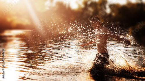Fototapeta a young man with a bare torso in black shorts running through the water with splashes against the sunset obraz na płótnie