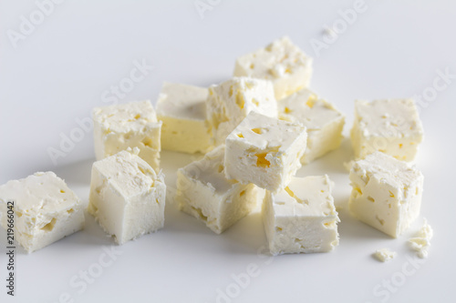 Feta cheese diced cubes stacked on white background - Close up image