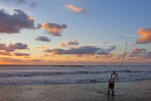 Scène De Pêche En Mer. Pêcheur En Surf Casting En Action Entrain De Lancer. Pêche Du Bord Sur Une Plage
