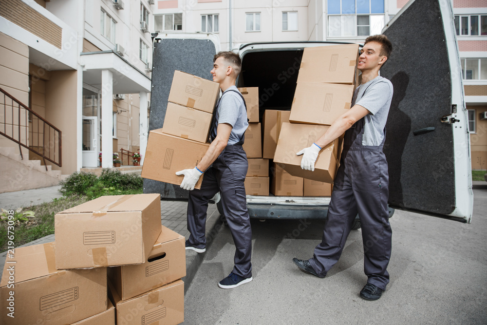 Fototapety, obrazy: Two young handsome smiling workers wearing uniforms are unloading the van full of boxes. The block of flats is in the background. House move, mover service.