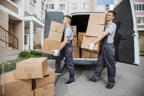 Fotografiet  Two young handsome smiling workers wearing uniforms are unloading the van full of boxes