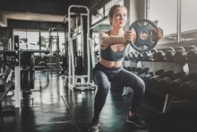 Woman Doing Workout With Weight Plate At The Gym