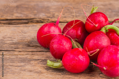 Pile of multiple radishes. Close up. Old vintage wooden desk table background.