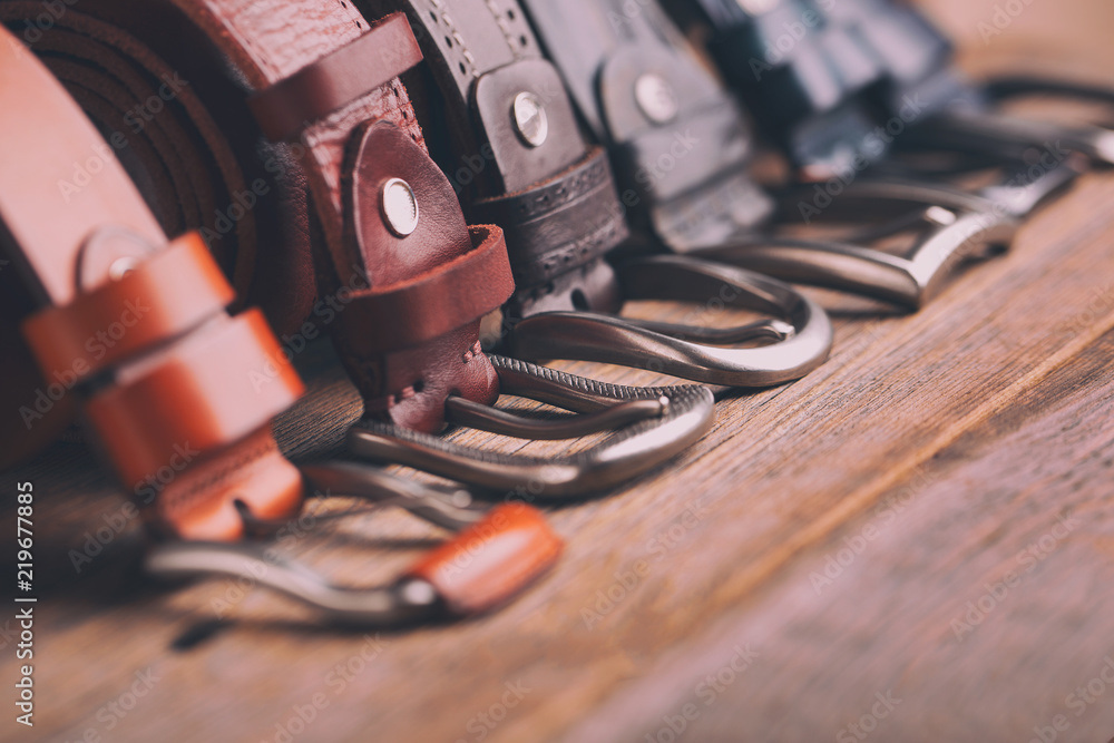 Fototapeta Leather belts on a wooden background. Fashionable leather belts.
