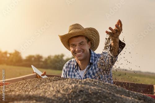Fotomural Happy farmer sitting in trailer full of sunflower seeds
