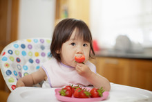 Baby Girl Eating Strewberry At Home Kitchen