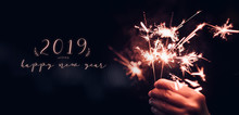 Hand Holding Burning Sparkler Blast With Happy New Year 2019 On A Black Bokeh Background At Night,holiday Celebration Event Party,dark Vintage Tone.