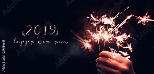 Fotografia  Hand holding burning Sparkler blast with happy new year 2019 on a black bokeh background at night,holiday celebration event party,dark vintage tone