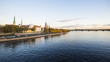 A view of the Old Town, the railway bridge and the TV Tower from the Daugava River promenade at sunset. Riga, Latvia
