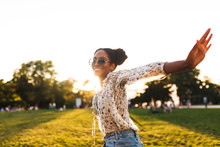 Beautiful Smiling African Girl In Sunglasses Joyfully Spending Time In City Park Isolated