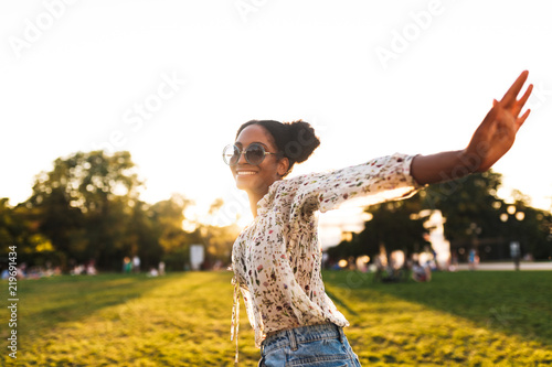 Fototapeta Beautiful smiling african girl in sunglasses joyfully spending time in city park isolated obraz