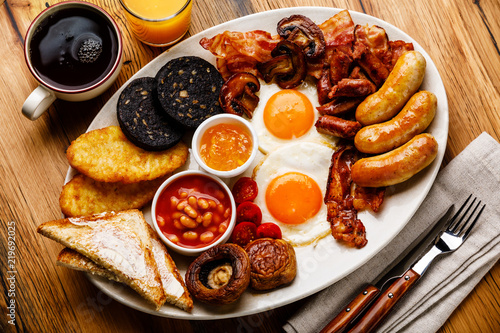 Full fry up English breakfast with fried eggs, sausages, bacon, black pudding, beans, toasts and tea on wooden background