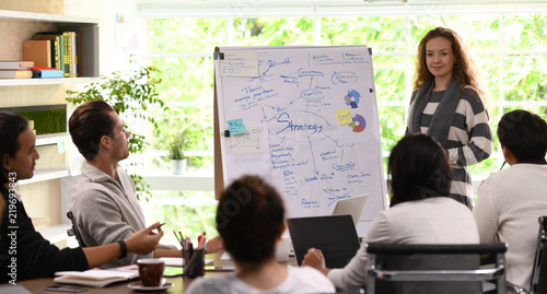 Fotografía  Young business woman giving presentation on future plans to his colleagues at of