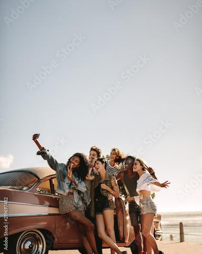 Obraz Multi ethnic friends taking a selfie near the car - fototapety do salonu