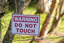 """A Warning Sign With The Words, """" DO NOT  TOUCH"""" On It. This Image Can Be Used To Represent The Concept Of Land Ownership.  Photo Taken In South Africa."""