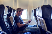 Man Is Reading Text Message On Mobile Phone And Speaking By Phone During Flying In The Airplane