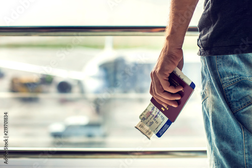 Obraz Closeup of man holding passports and boarding pass at airport. Traveling concept - fototapety do salonu