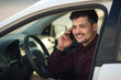 beautiful young guy in a shirt sitting in the car and talking on the phone