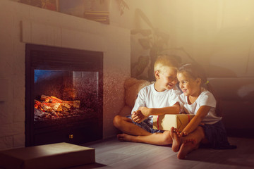 happy children with magic gift at home near fireplace